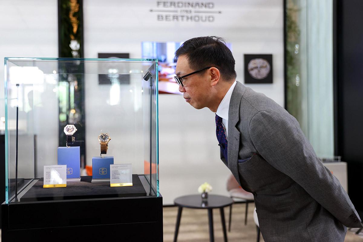 Un cinese guarda alcuni orologi di lusso a WandW Shanghai 2021